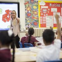 Teacher pointing at pupil with his hand up in classroom